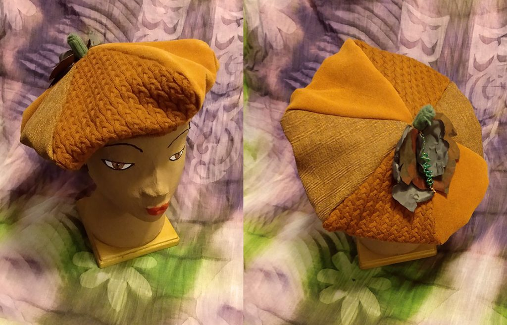 6-sectioned beret in shades of rust-orange, with fabric pumpkin leaf details, a knit pumpkin stem, and a beaded coiled vine. The hat is worn by a small head mannequin against a purple and green tie-dye background. This hat is the prize for a Twitter drawing, to be held on 10/23/21.
